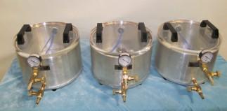 Three aluminum rounds with acrylic lids for dispensing liquids under vacuum.
