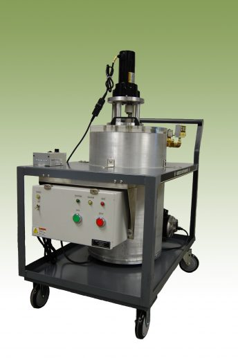 Round vacuum chamber with electric mixer attached. Chamber mounted in a cart